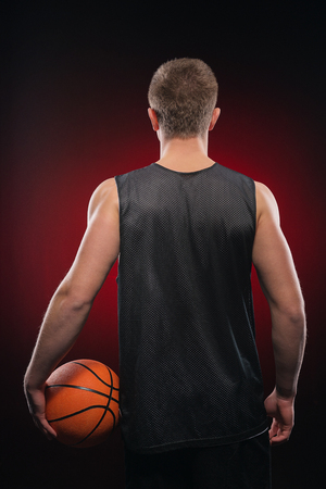 �aucasian: Back shot photo of basketball player holding the ball at his side on red background