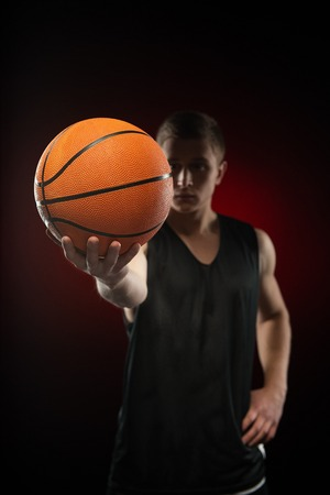 aucasian: Close-up photo of ball in serious young Caucasian basketball athlete hand