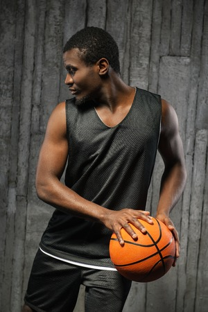 Afro-american young muscular male basketball player holding ball against grunge background