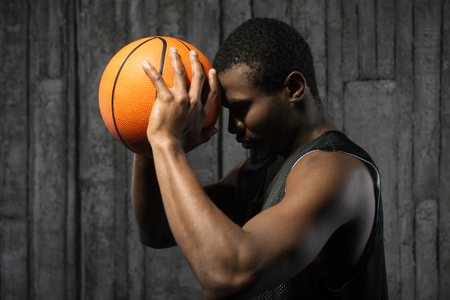 the sincerity: Afro-american male basketball player pressing ball to his forehead on grunge background.