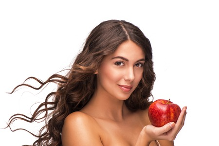 �aucasian: Beautiful young woman with curly hair holding red apple, isolated on white background.