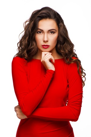 aucasian: Gorgeous woman with curly hair in red dress looking severely at camera, isolated on white background