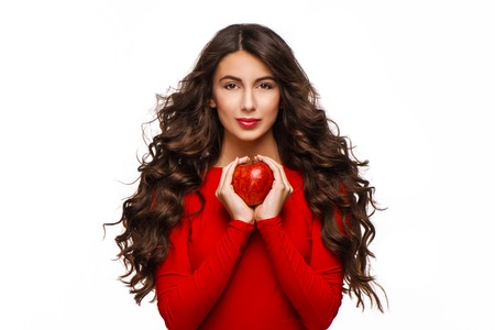 aucasian: Beautiful young woman with curly hair holding red apple, isolated on white background.
