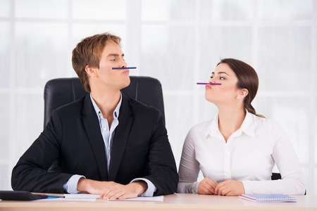 Young business woman and man having fun on working place with pen upper lips