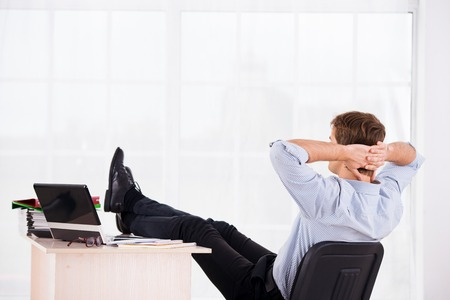 relaxed business man: Back side photo of relaxed business man with hands up reposing on headchair. Office big window background Stock Photo