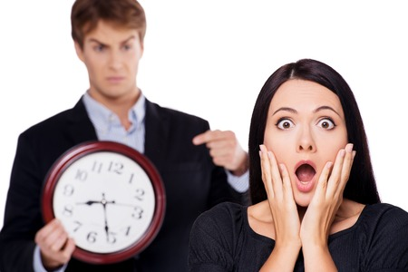 aucasian: Frightened business woman is late on work, with angry boss on background. Concept for lateness