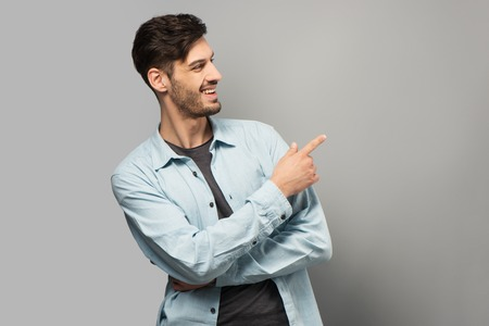 aucasian: Handsome young man smiling and pointing at something with finger, standing on grey background