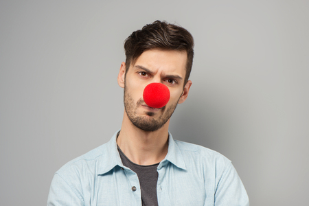 clown nose: Sad young man wearing clown nose, standing on grey background Stock Photo