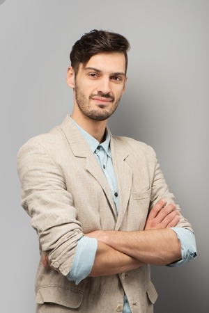 �aucasian: Casual young man looking at camera, standing on grey background