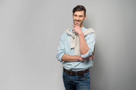 �aucasian: Smiling young man looking at camera, standing on grey background Stock Photo