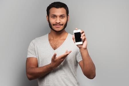 Homem da ra�a misturada nova que aponta no telefone inteligente, de p� no fundo cinzento