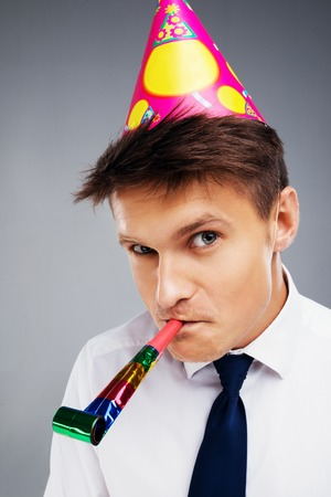 aucasian: Funny close up photo of young office manager with party hat and blower