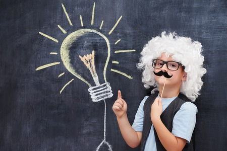 enlightment: Cheerful boy with fake mustage and Einstein  wig point on bulb visualised on the blackboerd