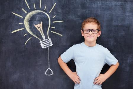 dessin enfants: �l�ve intelligente Confiant stending ageinst blacbourd avec le signe ampoule idaea