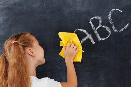 diligent: Cute diligent ginger school-girl cleaning blackboard  with yellow rag