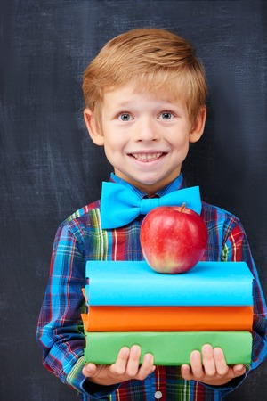 grade school age: Redhead pupil expressing inspiration and positivity with multicolour book and an apple, diligent student concept