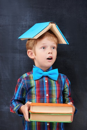 diligent: Redhead primary-school pupil witn colour books inhalr in anticipation of future hard working, diligent student concept