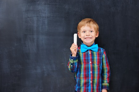 junior education: Cute ginger boy holding a chalk against blackboard background. Diligent student concept