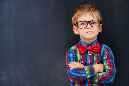pre school: Cute ginger boy standing against blackboard background