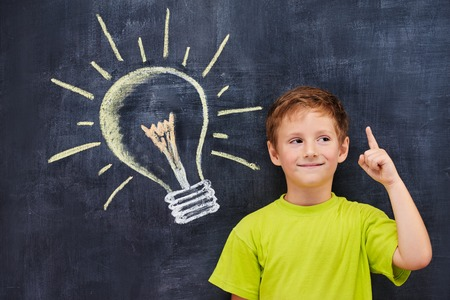 Conceptual portait of redhead primary age school boy with pictured lightbulb