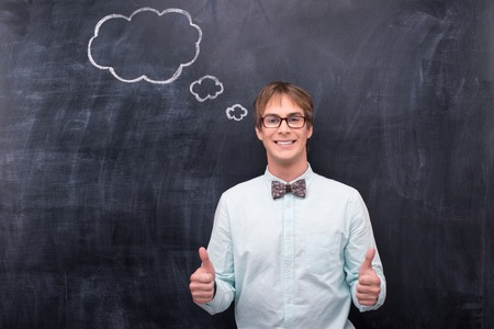 Smiling man in glasses showing thumbs up Stock Photo