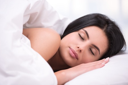 dark haired woman: Close up photo of beautiful young dark haired woman. She sleeping comfortably curled under a white blanket