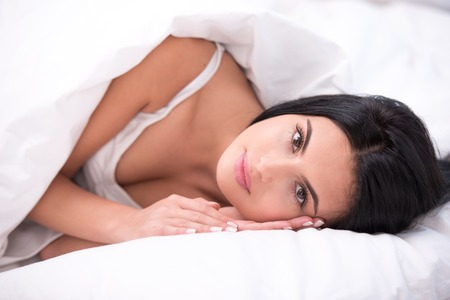 dark haired: Close up photo of beautiful young dark haired woman. She is comfortably curled under a white blanket. Woman looking at camera Stock Photo