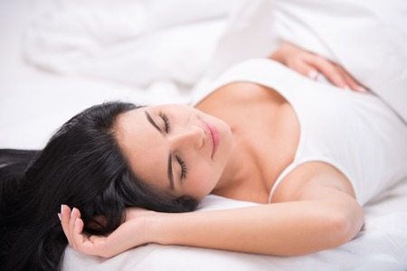aucasian: Photo of beautiful young dark haired woman. She sleeping comfortably curled under a white blanket