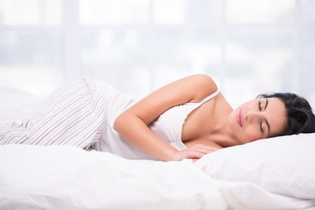 Beautiful young dark haired woman sleeping on a white bed wearing striped pyjamas