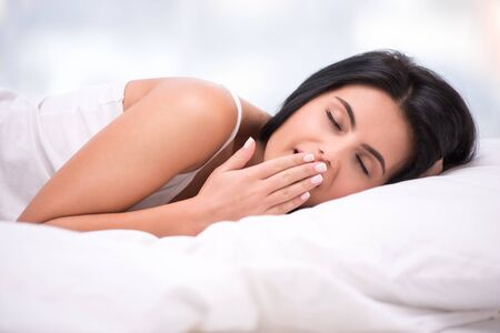 dark haired woman: Close up photo of beautiful young dark haired woman. She yawning and lying under a white blanket