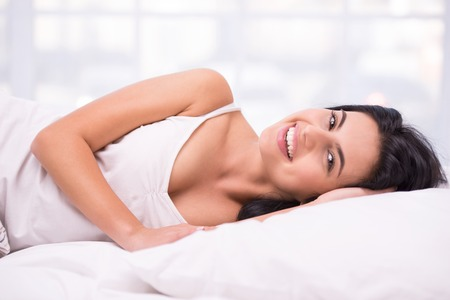 aucasian: Close up photo of beautiful young dark haired woman. She smiling and lying under a white blanket