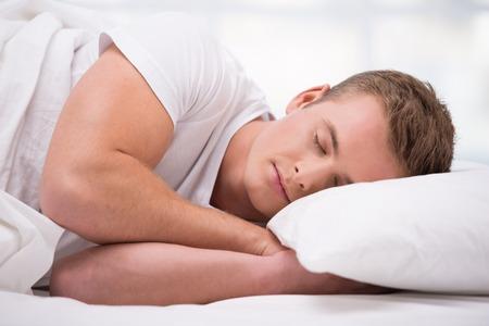 Close up Foto von schönen jungen Mannes. Er schlief bequem unter einer weißen Decke eingerollt Standard-Bild