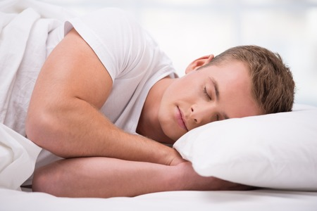 Close up photo of handsome young man. He sleeping comfortably curled under a white blanket Stock Photo