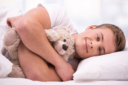 aucasian: Close up photo of handsome young man. He is comfortably curled under a white blanket and holding teddy bear Stock Photo