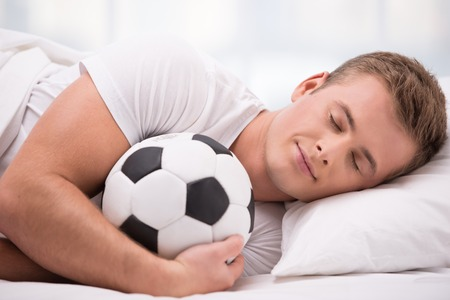 aucasian: Close up photo of handsome young man. He is comfortably curled under a white blanket and holding soft ball Stock Photo