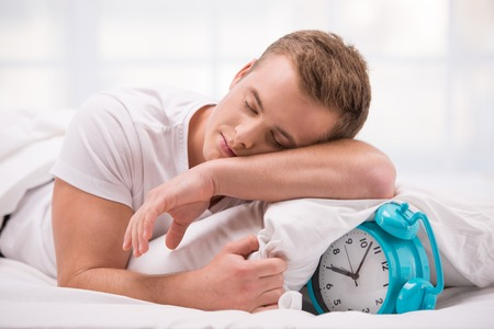 aucasian: Close up photo of tired and sleepy young man. He lying in white bed with blue alarm clock under pillow