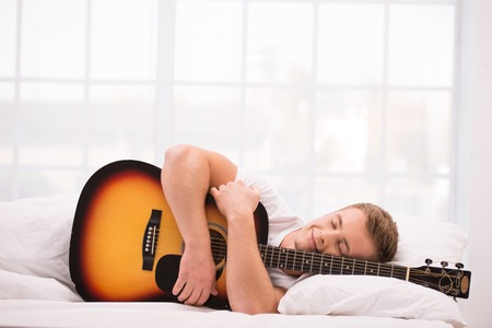 aucasian: Photo of handsome young man. He is comfortably curled under a white blanket and holding guitar
