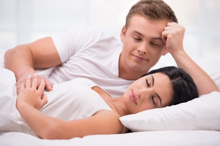 Young couple lying in white bed early in the morning. Handsome man looking at his sleeping wife Banco de Imagens