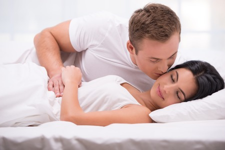 dark haired woman: Young couple lying in white bed early in the morning. Handsome man kissing his sleeping wife