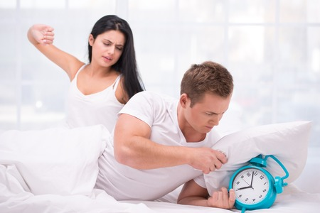 Photo of young sleepy couple early in the morning. They waking up by an alarm clock ringing