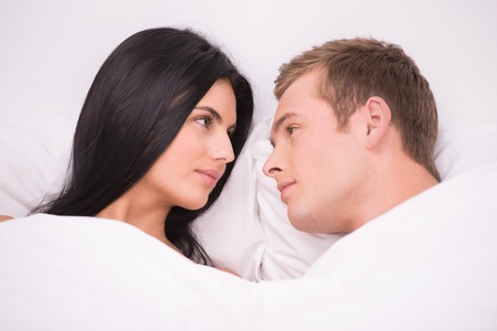 �aucasian: Young couple lying in white bed early in the morning under white blanket and looking at each other Stock Photo