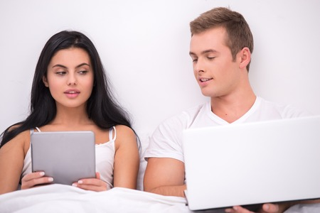 Photo of young couple sitting in white bed under white blanket. They using tablet computer and laptop. Man and woman looking at each others computers photo