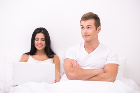 Funny picture of young couple sitting in white bed under white blanket. Woman using laptop and man expressing dissatisfaction photo