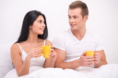 aucasian: Young couple sitting under white blanket early in the morning and having their breakfast in bed. Man and woman drinking tea or coffee