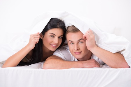aucasian: Photo of happy smiling young couple hiding under white blanket and looking at camera