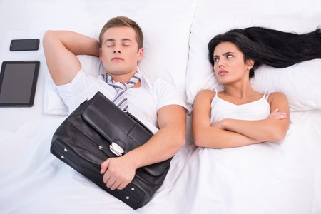 aucasian: Top view photo of young couple lying in bed under white blanket with electronic gadgets. Angry woman looking at sleeping husband who holding briefcase
