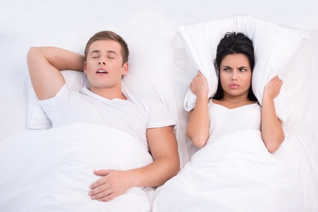 husband and wife: Top view photo of young couple lying in bed under white blanket. Woman is angry because of snoring husband