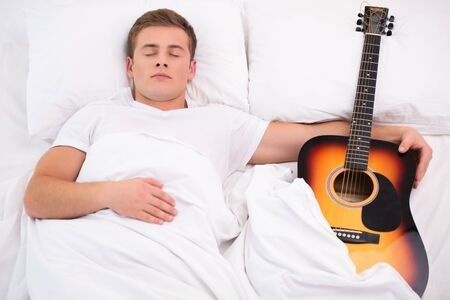 Top view photo of handsome young man sleeping and holding guitar Stock Photo