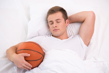 �aucasian: Top view photo of handsome young man. He holding basketball while sleeping