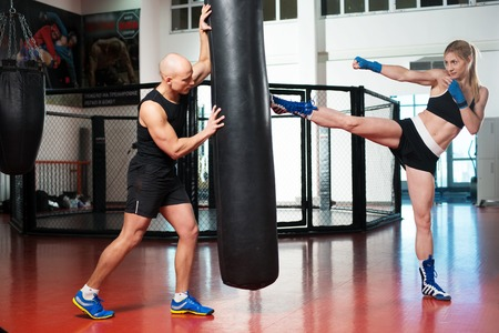 Man and woman doing sport exercises at the fitness gym and training next to a punching bag